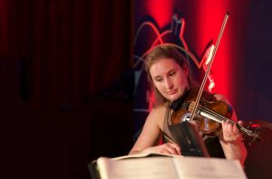 Violinist entertaining guests on stage, with event branding on the backdrop